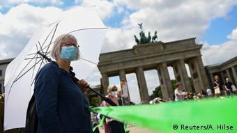 Женщина в маске на фоне Бранденбургских ворот в Берлине
