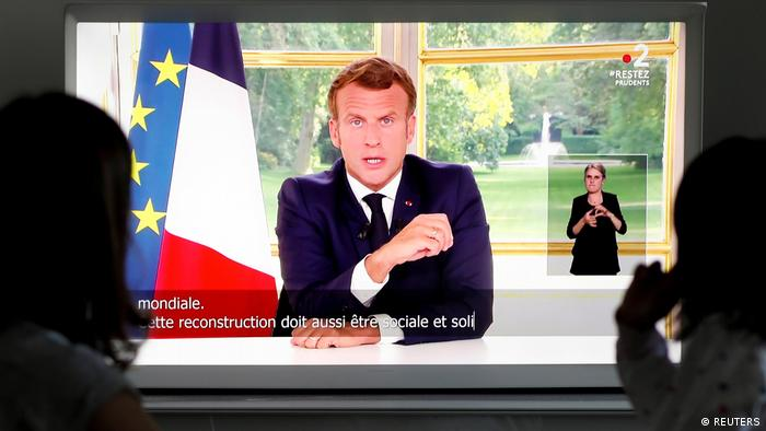 A family watch French President Emmanuel Macron during a televised address to the nation