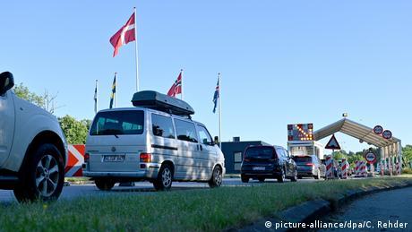 Autos hacen fila ante un puesto de frontera.