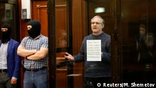Former U.S. Marine Paul Whelan, who was detained and accused of espionage, holds a sign as he stands inside a defendants' cage during his verdict hearing in Moscow, Russia June 15, 2020. REUTERS/Maxim Shemetov