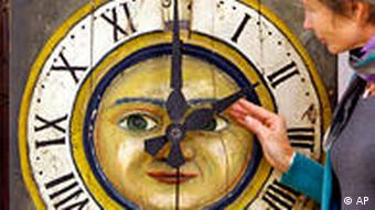 Woman readjusting a clock with a sun as its face