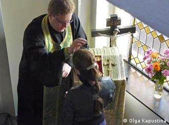 Russisch-orthodoxer Gottesdienst in der Maria-Obhut-Kirche Düsseldorf. Priester Rybakow und ein Mädchen bei der Beichte im Kirchenflur Foto: Olga Kapustina, Oktober 2009