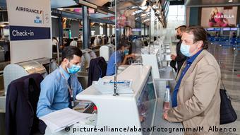Сотрудник аэропорта Милана регистрирует на рейс авиапассажира