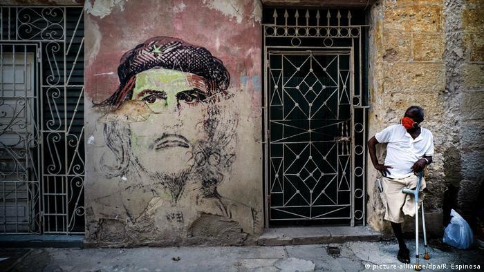 Homem de máscara protetora, ao lado de grafite de Che Guevara