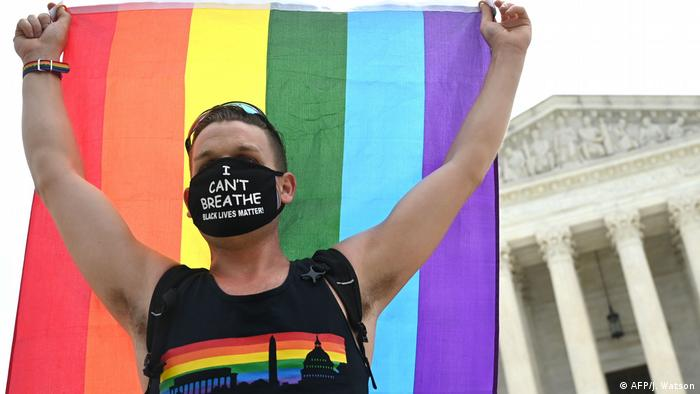 A man waves a rainbow flag in front of the US Supreme Court