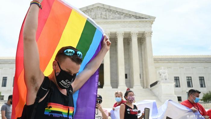 Homem levanta bandeira LGBT em frente à Suprema Corte dos EUA