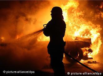 Feuerwehrmann löscht brennendes Auto (Foto: dpa)