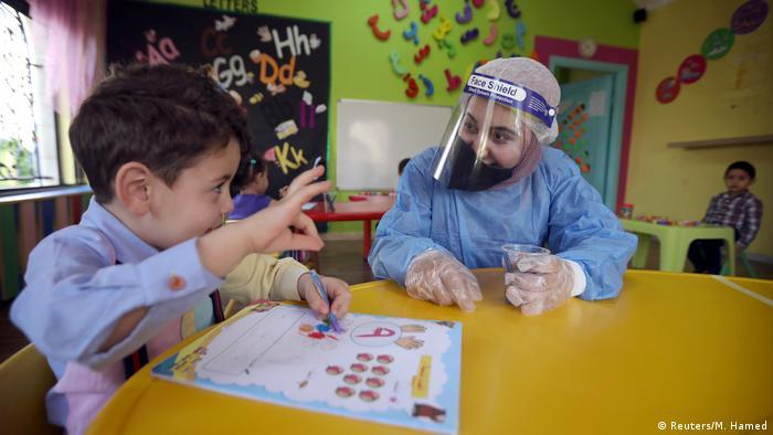 Lehrerin mit Schutzmaske betreut ein Kind ohne Maske in einem Kindergarten in Amman, Jordanien