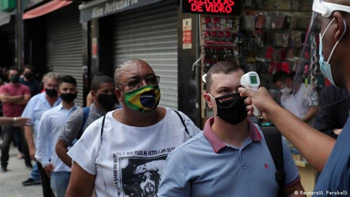 Homem mede temperatura de pessoas de máscara