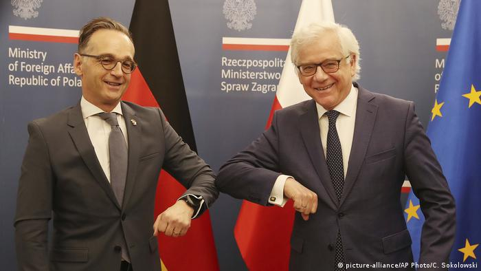German Foreign Minister Heiko Maas,left, and Polish Foreign Minister Jacek Czaputowicz greet each other with an elbow bump, used instead of a handshake during the coronavirus pandemic, in Warsaw, Poland, Tuesday, June 16, 2020. (picture-alliance/AP Photo/C. Sokolowski)
