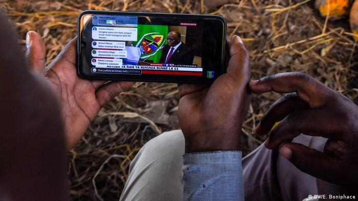 Two people watch a speech by Tanzania's President John Magufuli on a smartphone
