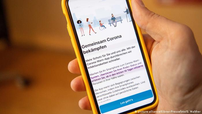 Someone holding a smartphone showing the German Corona tracing app