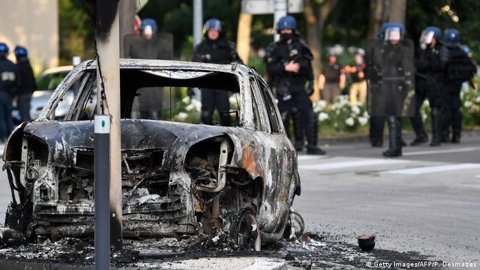 Сгоревшая в ходе уличных беспорядков машина в Дижоне