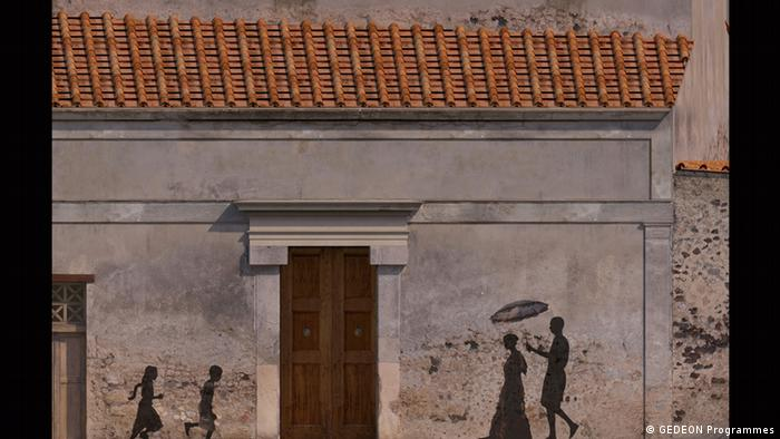 Rebuilt house with shadows of pedestrians and children playing along a wall , part of the Pompeii exhibition in Paris' Grand Palais (GEDEON Programmes)