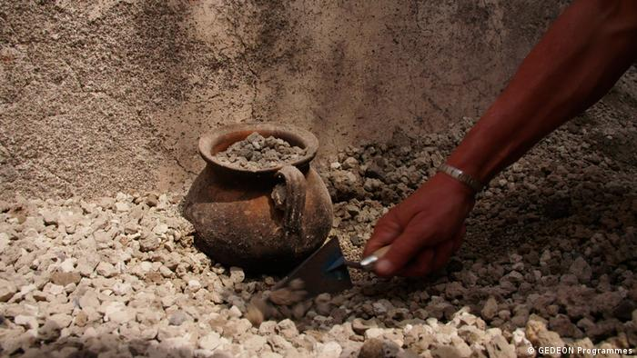 A woman's hand digging out in pot in a photo shown in the Pompeii exhibition (GEDEON Programmes)