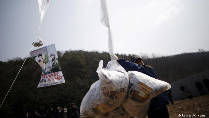 A North Korean defector living in the South and leader of an anti-North Korea civic group, holds a balloon containing leaflets denouncing North Korean leader Kim Jong Un, near the demilitarized zone separating the two Koreas in Paju, South Korea, March 26, 2016.