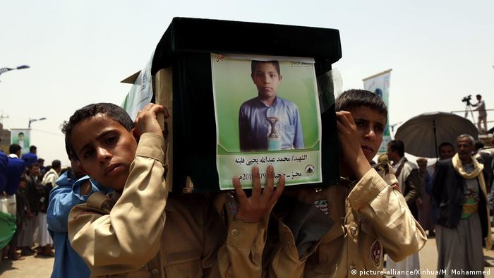 Boys carry the coffin of a child who died in Saudi airstrikes that hit passenger buses and killed dozens in August 2018
