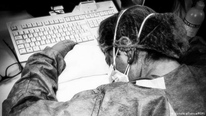 Enfermeira italiana Elena Pagliarini dorme sobre computador no trabalho
