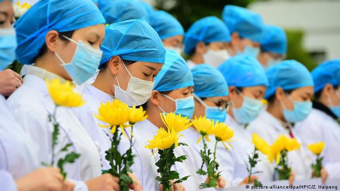 Nurses and doctors at Huichang People's Hospital pay tribute as China holds national mourning for those who died of the coronavirus in Ganzhou
