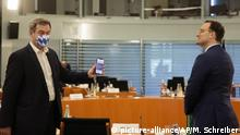Bavarian Prime Minister Markus Soeder, left, wears a face mask with Bavarian's white and blue diamond pattern as he shows his cell-phone displaying the German corona-warning app, to Health Minister Jens Spahn, right, prior to a meeting with German Chancellor Angela Merkel and German federal state governors at the chancellery in Berlin, Germany, Wednesday, June 17, 2020 about measures on the coronavirus and COVID-19 pandemic. (AP Photo/Markus Schreiber, Pool) |