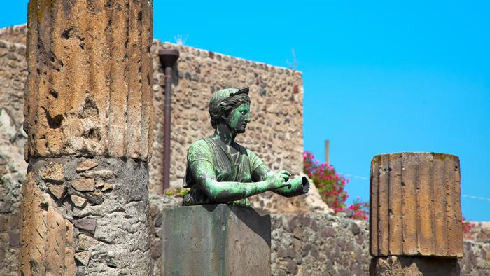 Statue of the goddess Diana next to columns in Pompeii