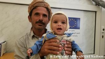 A man in Yemen holds up a malnourished baby (Save the Children/Majed Nadhem)
