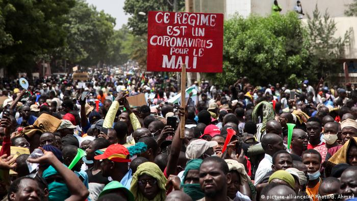 A placard in the middle of a crowd reads This regime is a coronavirus for Mali (picture-alliance/AP Photo/B. Ahmed)