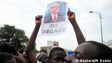 A supporter of the Imam Mahmoud Dicko holds a poster of Mali's President Ibrahim Boubacar Keita during a mass protest to demand his resignation at the Independence Square in Bamako, Mali June 5, 2020. REUTERS/Matthieu Rosier