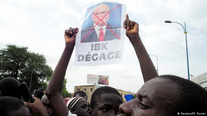 A supporter of the Imam Mahmoud Dicko holds a poster of Mali's President Ibrahim Boubacar Keita during a mass protest to demand his resignation