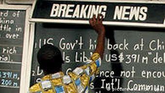 Alfred Sirleaf writes the news on a blackboard