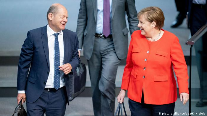 Finance Minister Olaf Scholz and Chancellor Angela Merkel walking happily down the stairs at the German parliament after agreeing on a stumulus package