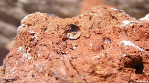 A water droplet pooled together on a stone
