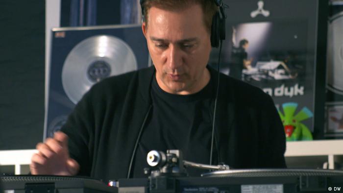 Van Dyk joue de la musique derrière une platine.