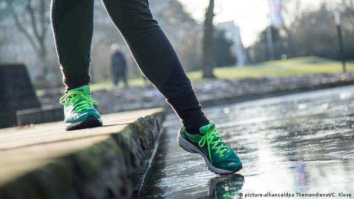 A person tests ice by putting their foot out on it (picture-alliance/dpa Themendienst/C. Klose)
