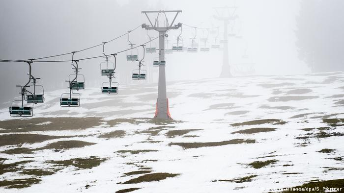 ski lift, empty, with a few patches of snow underneath on the ground (picture-alliance/dpa/S. Pförtner)