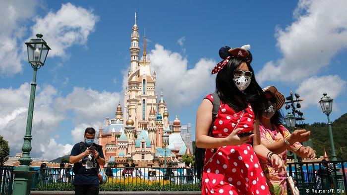 Disneypark in Hongkong mit drei Besuchern mit Masken vor Phantasieschloss - (Reuters/T. Siu)