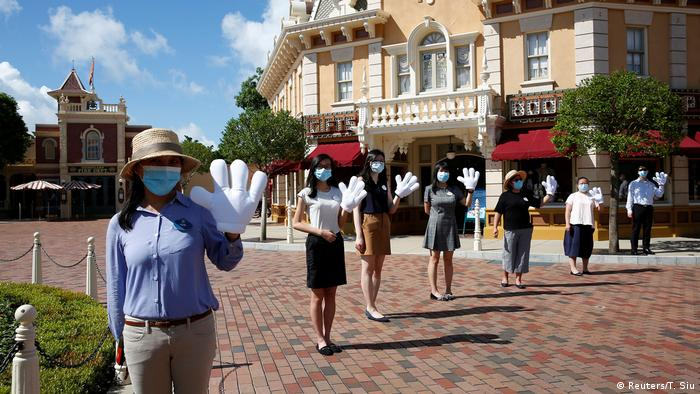 Employees wave to visitors at the Disneyland theme park after it reopened following a shutdown due to the coronavirus disease (COVID-19) in Hong Kong, China June 18, 2020. (Reuters/T. Siu)