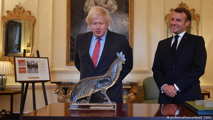 Boris Johnson and Emmanuel Macron look at a cock, which General Charles De Gaulle gave to Lady Churchill