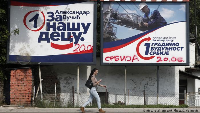 Woman walking past election billboards (picture-alliance/AP Photo/D. Vojinovic)