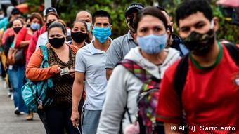 Очередь людей в масках возле станции метро в Медельине (Колумбия)