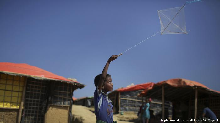 A boy flies his kite outside his family's tent in the Kutupalong refugee camp in Bangladesh (2017)