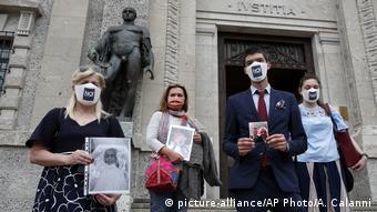 Жители Бергамо с фотографиями умерших родственников на ступенях суда в Бергамо