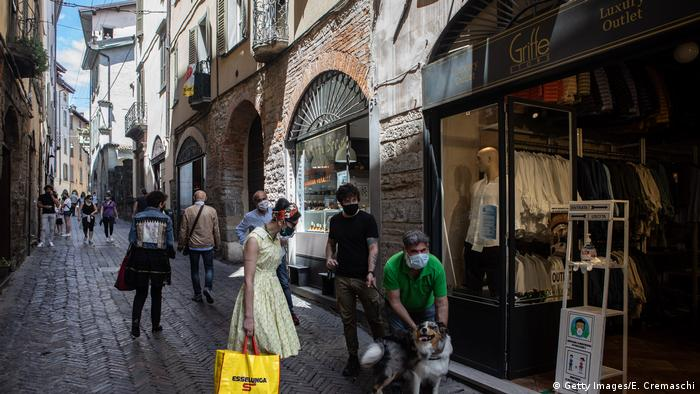 Some people pet a dog in the streets in the Upper Town in Bergamo