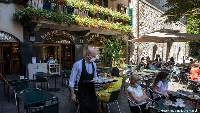 A waiter serves some customers at Bar Marianna in Bergamo