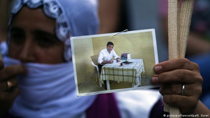 Woman holding up photograph of Selahattin Demirtas