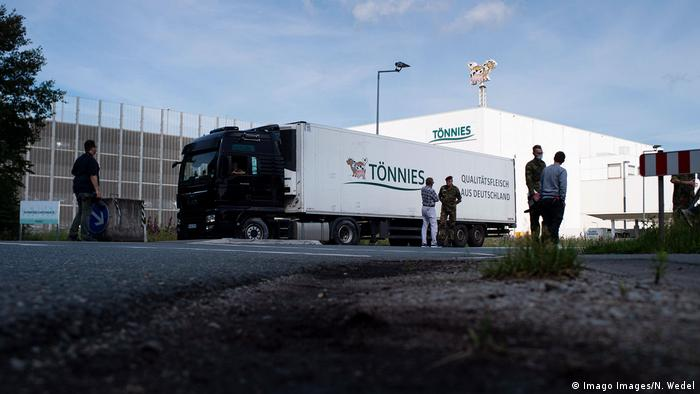 A lorry is parked outside the Tönnies factory with people standing nearby