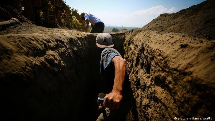 Un hombre de espaldas cava una fosa buscando restos de personas desaparecidas en Guadalajara, Mëxico.