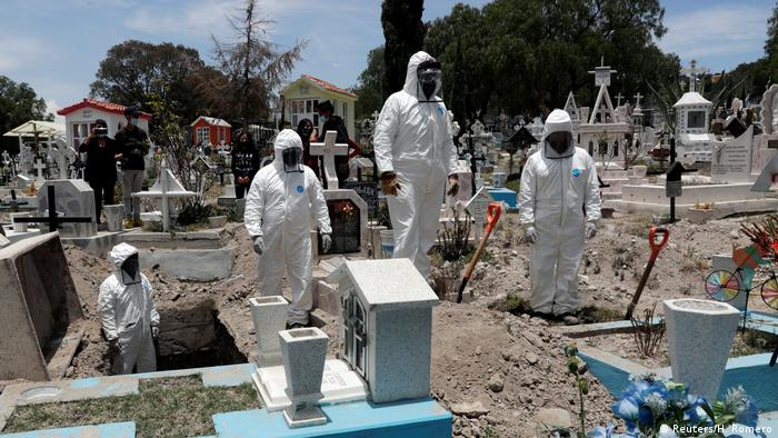 Cemetery workers wearing protective suits complete the burial of a man, who died of the coronavirus disease