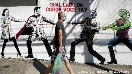 Coronavirus   Brasilien Wandgemälde mit Tauziehen zwischen Gesundheitspersonal Präsident Bolsonaro (picture-alliance/AP Photo/A. Penner)