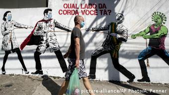 Мужчина в маске и граффити в Сан-Паулу о борьбе врачей с вирусом SARS-CoV-2